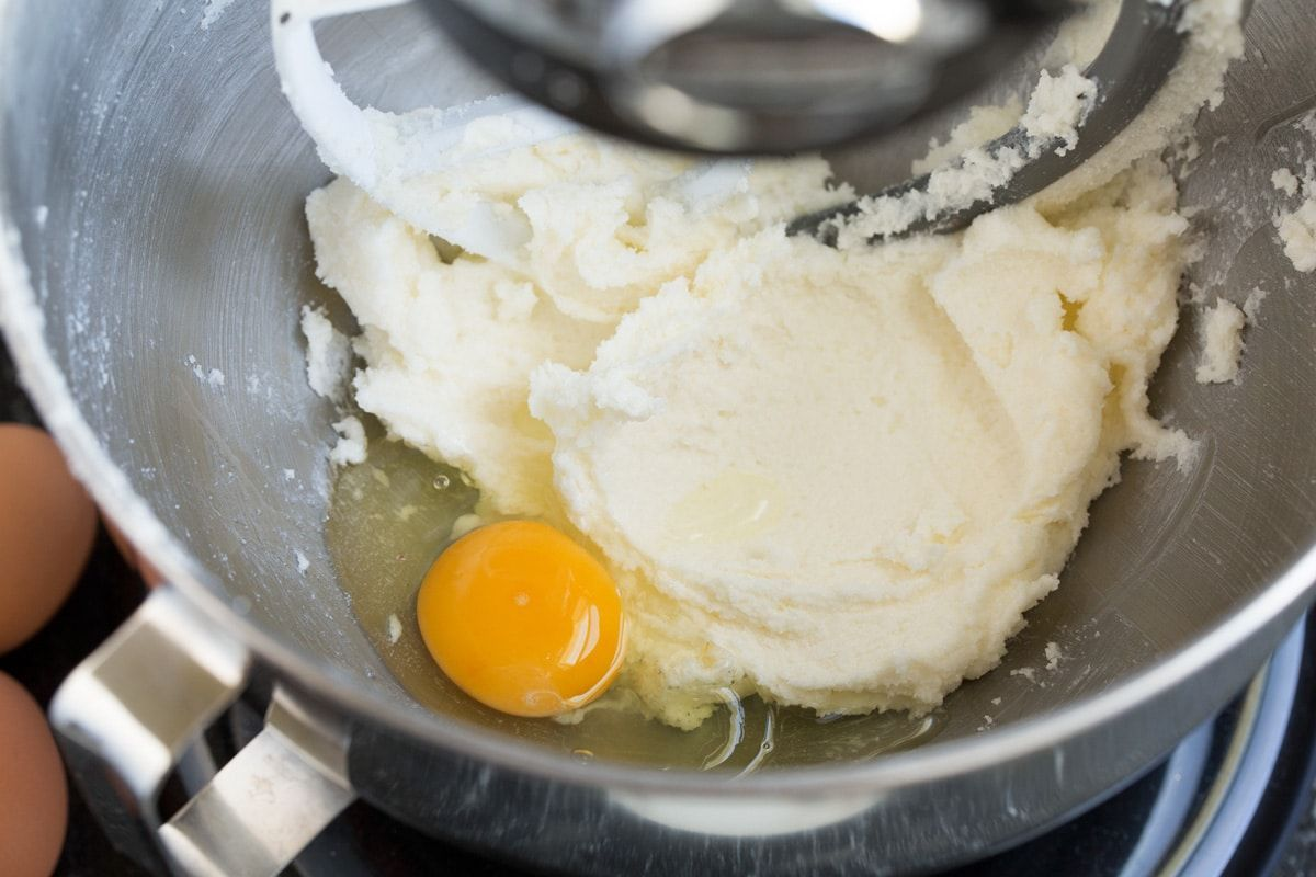 Adding egg to butter sugar mixture in mixing bowl.