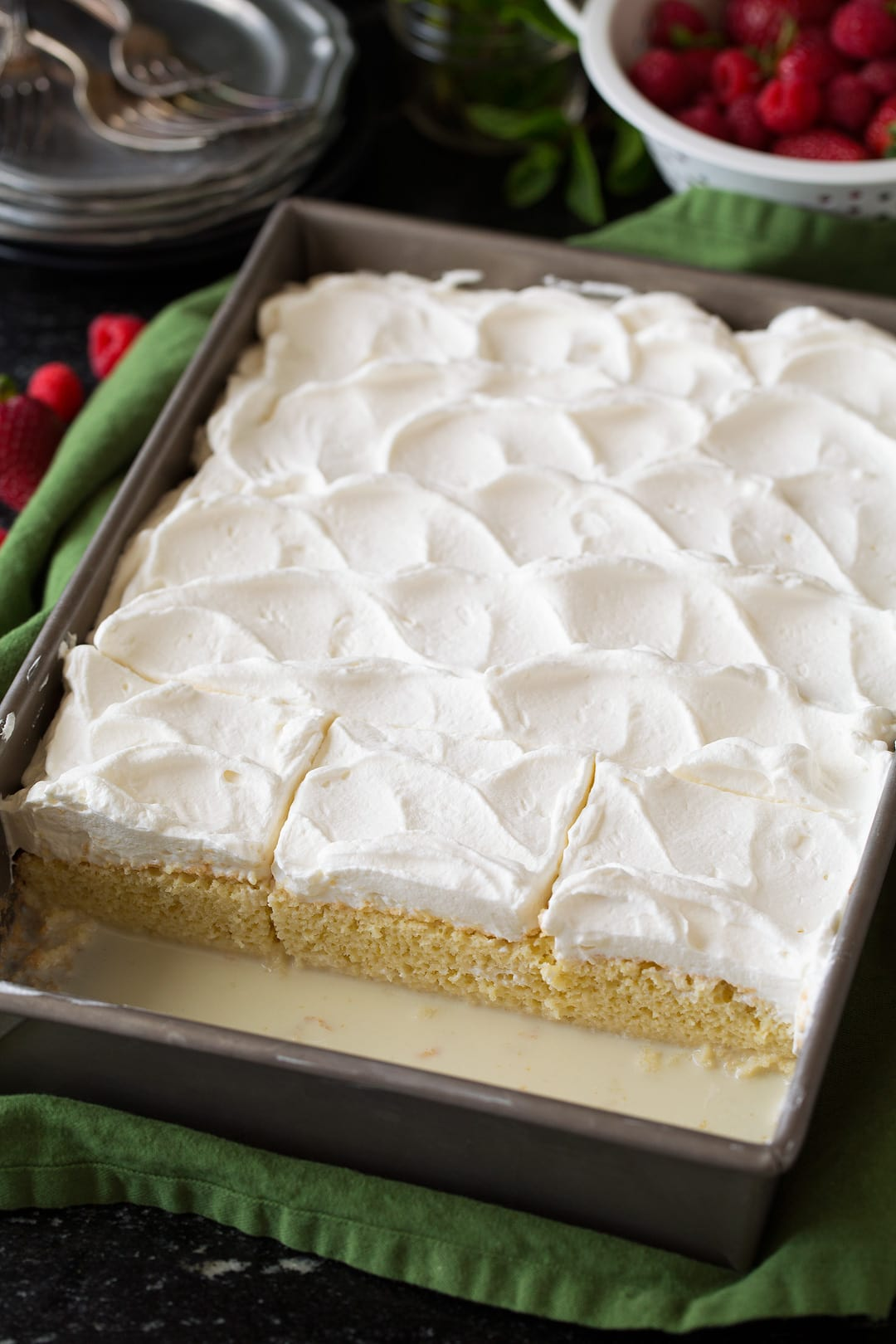 Tres Leches Cake in baking dish, shown after adding whipped cream topping.