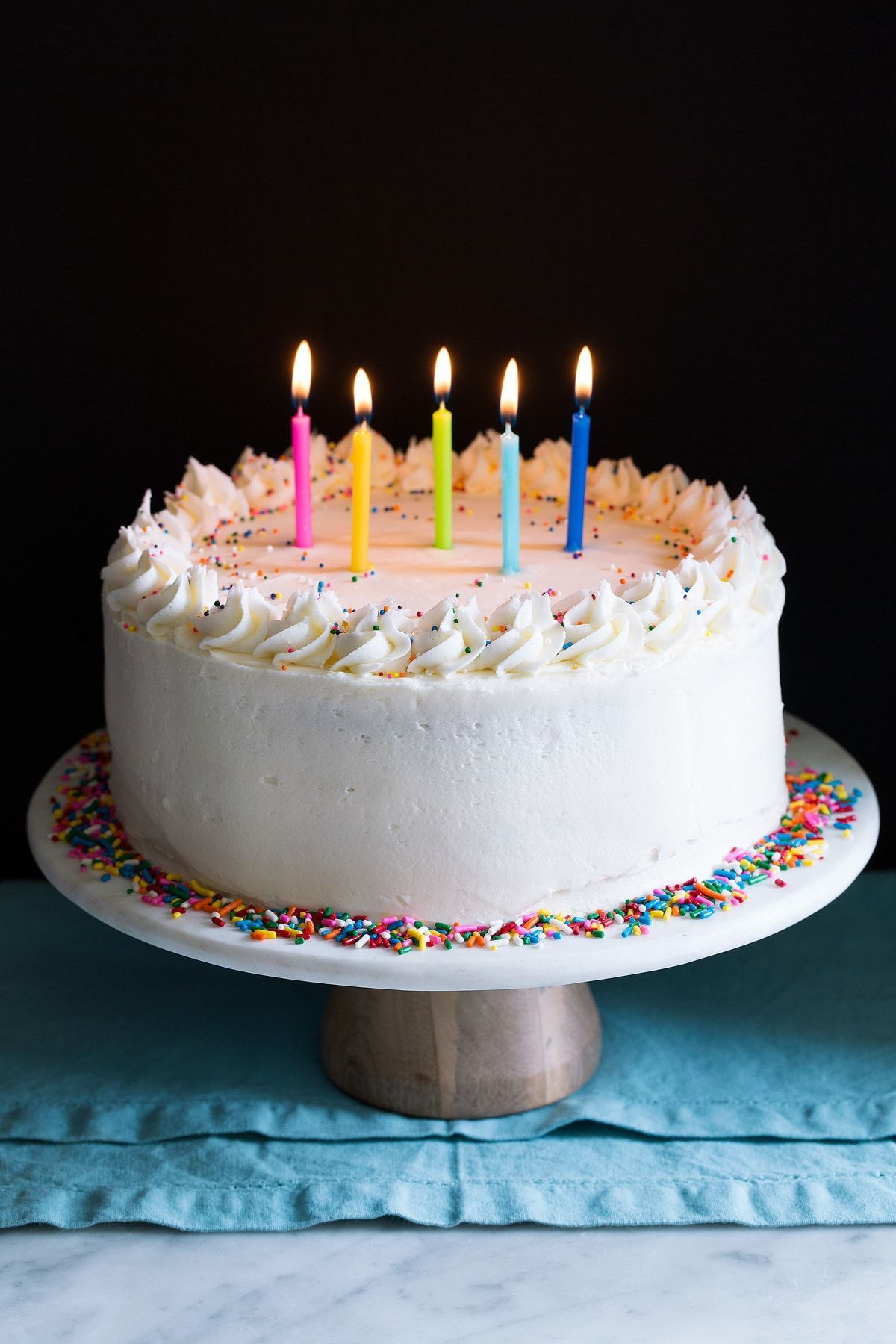 Whole birthday cake on a cake stand garnished with sprinkles and topped with lit birthday candles.