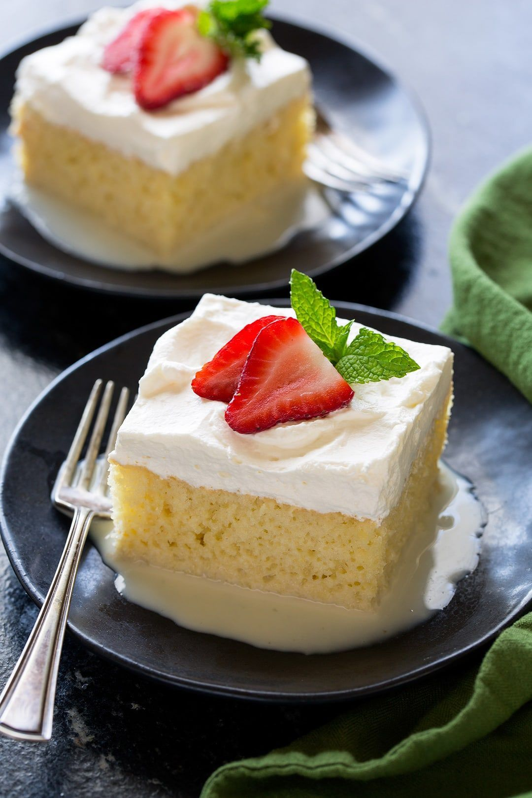 Slice of Tres Leches Cake on a small black dessert plate. Cake is a creamy yellow color with a white whipped cream frosting. It's garnished with fresh strawberry slices and mint on top.