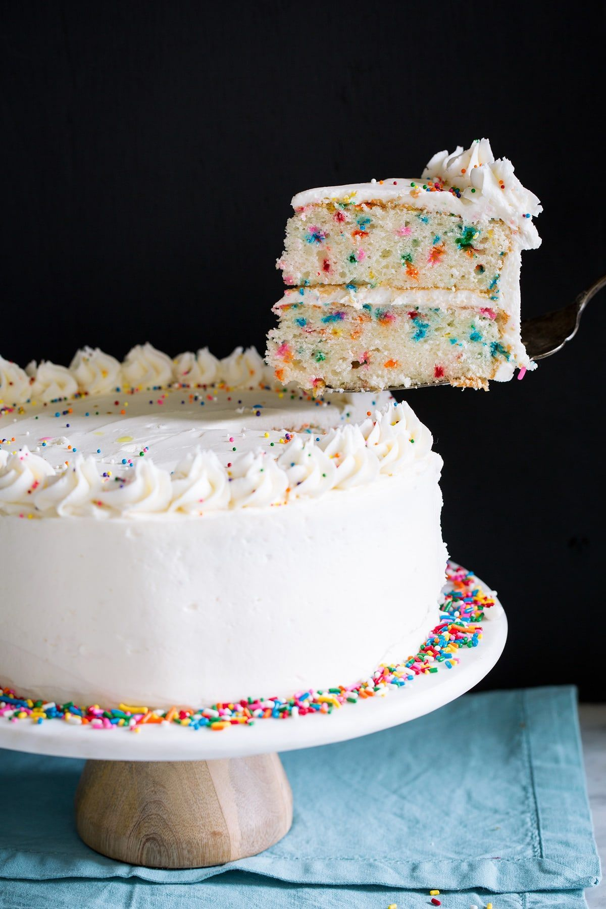Lifting a single slice with a serving spatula from a whole cake.